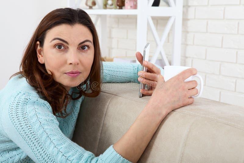 svart telefon för kommunikationsbegreppsmottagare Attraktiv kvinna som ser hennes smarta telefon och ler, medan sitta på soffan h royaltyfri bild