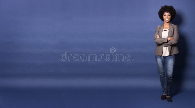 Svart tillfällig kvinna på blå bakgrund royaltyfria foton