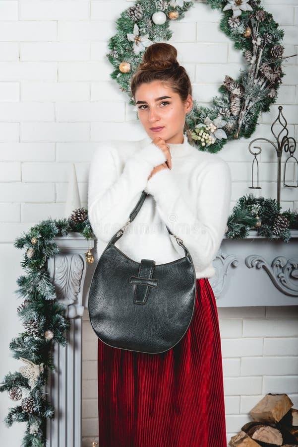 Svart trendig handväska i händer av den ursnygga unga kvinnlign i en röd kjol och en vit sweater på dekorerad jul arkivbilder