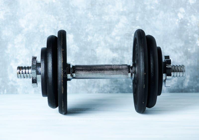 Svart tung hantel på lantlig träbakgrund Kondition- eller bodybuildingbakgrund royaltyfria foton