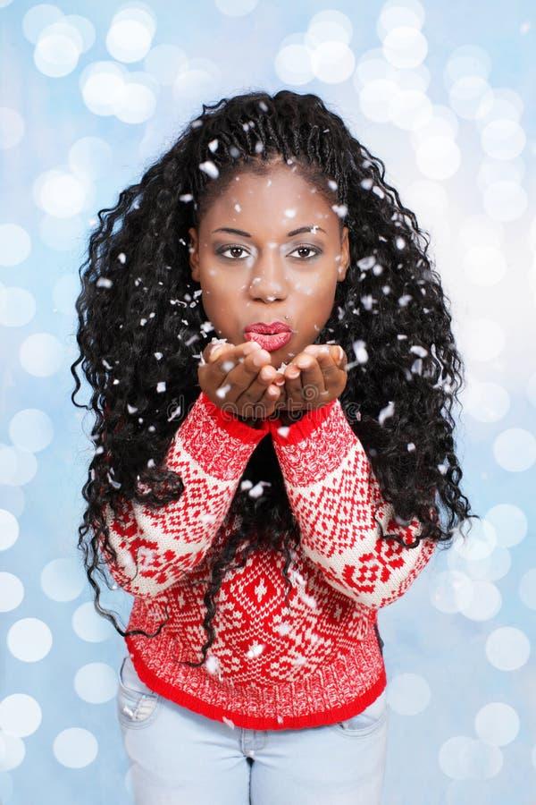 Svart ung kvinna som blåser snöflingor royaltyfri fotografi