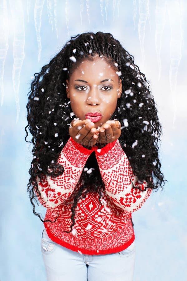 Svart ung kvinna som blåser snöflingor royaltyfri bild