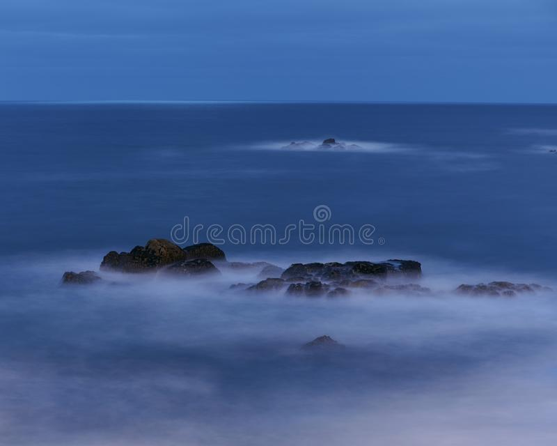 Svart vaggar på den blåa timmen på havet Lugna, mjukt och kallt arkivfoto