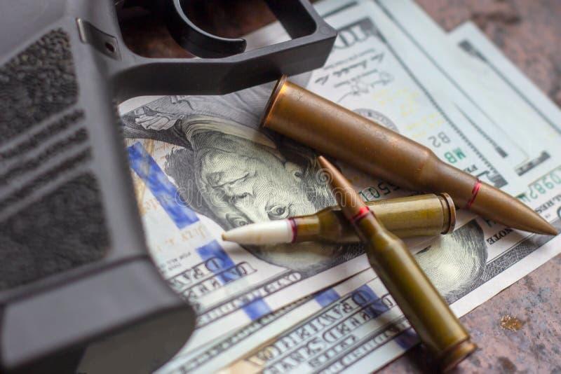Svart vapen och kulor på amerikansk dollarbakgrund Militär bransch, krig, global vapenhandel, vapenförsäljning, avtalsdödande arkivfoto