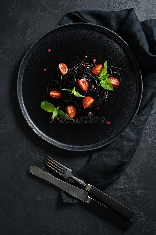 Svart vegetarisk pasta med basilika och k?rsb?rsr?da tomater Svart bakgrund, b?sta sikt royaltyfri fotografi