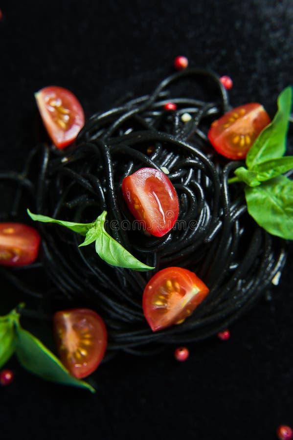Svart vegetarisk pasta med basilika och k?rsb?rsr?da tomater Svart bakgrund, b?sta sikt royaltyfria bilder