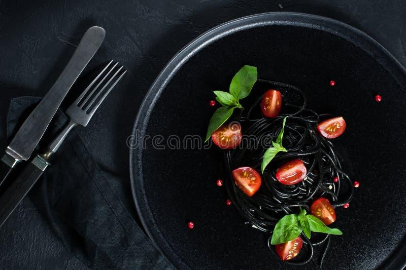 Svart vegetarisk pasta med basilika och k?rsb?rsr?da tomater Svart bakgrund, b?sta sikt royaltyfri foto