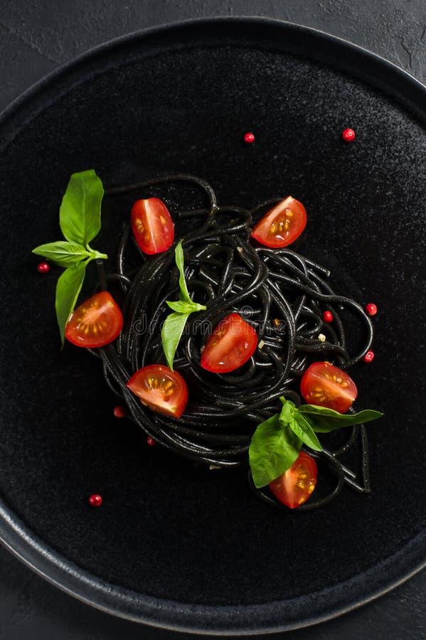 Svart vegetarisk pasta med basilika och k?rsb?rsr?da tomater Svart bakgrund, b?sta sikt arkivbild