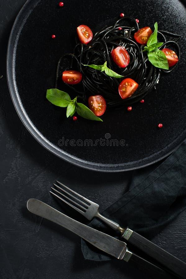 Svart vegetarisk pasta med basilika och k royaltyfria bilder