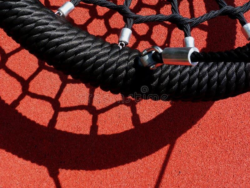 Svart vinylrepgunga i lekplats med rött rubber mattt arkivbild