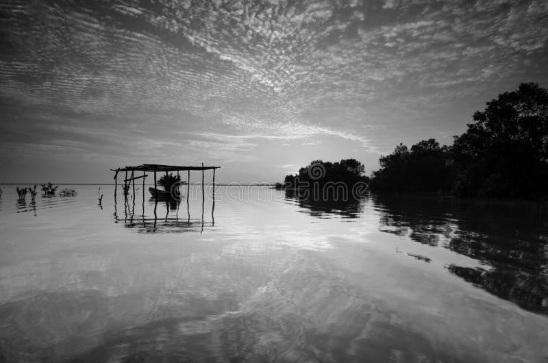 Svart & vit bild f?r konst av det h?rliga landskapet av stranden p? morgonen Fiskarefartyg och moln som reflekterar i vattnet royaltyfri bild