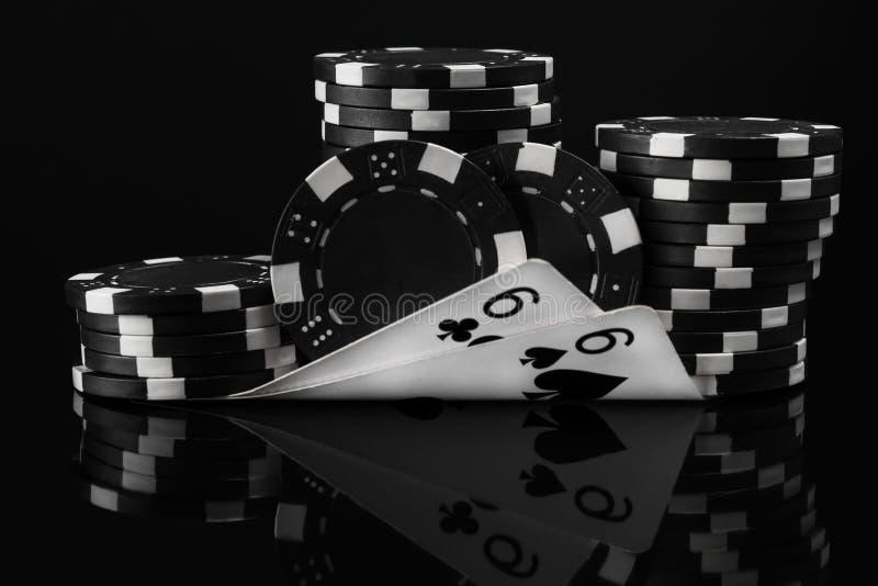 Svart vit idé av pokerchiper och pokerkort i poker på en svart arkivbild