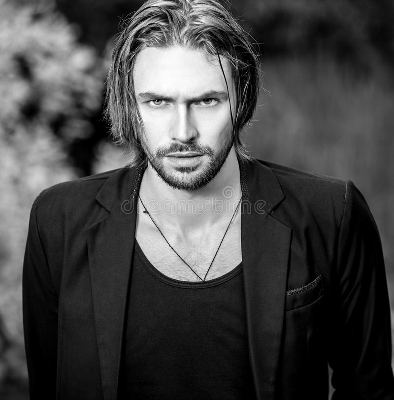 Svart-vit utomhus- stående av den stiliga mannen för elegant långt hår royaltyfri foto