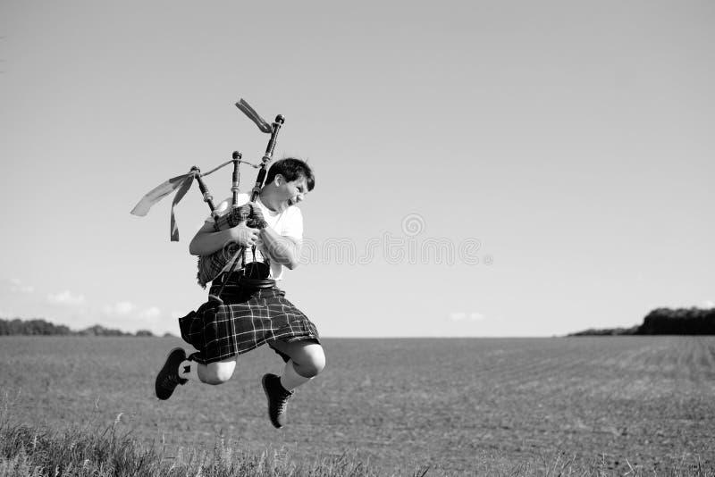 Svart vitt fotografi av mannen som högt utomhus hoppar med rör i skotsk traditionell kilt på sommarfält arkivbilder