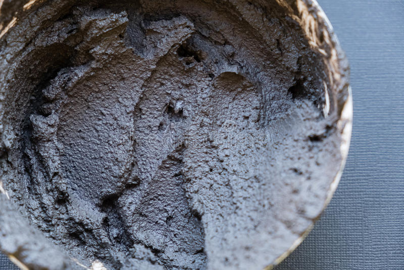 Svart vulkanisk kosmetisk lera i en bunke kosmetiskt leratexturslut upp lösning av kosmetisk leraabstrakt begreppbakgrund arkivbild