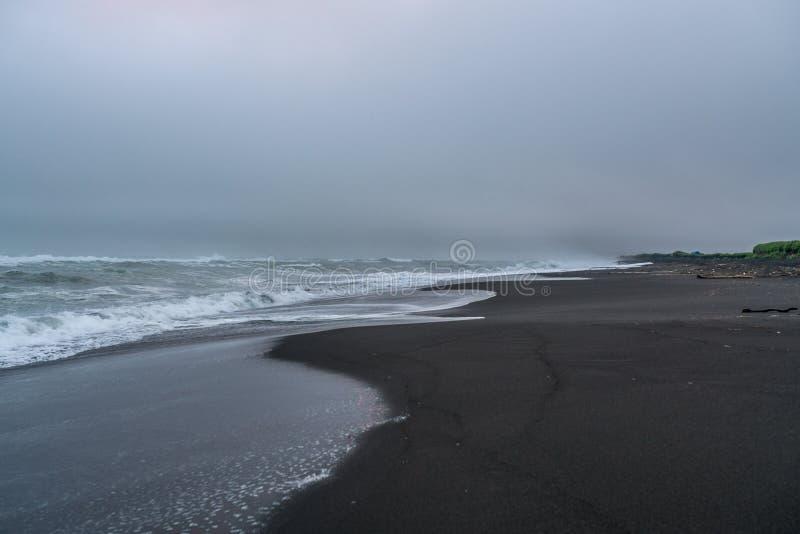 Svart vulkanisk sand på den Khalaktyrsky stranden av det Stillahavs- på den Kamchatka halvön, nära Petropavlovsk-Kamchatsky, Ryss royaltyfri fotografi