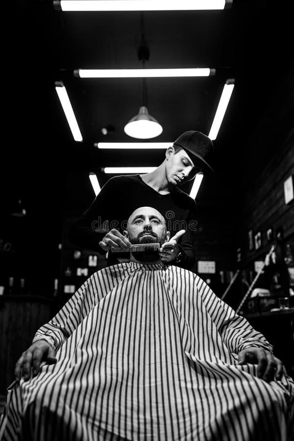 svart white Den stilfulla frisersalongen Modebarberaren ordnar skägget av den brutala mannen som sitter i fåtöljen arkivfoto