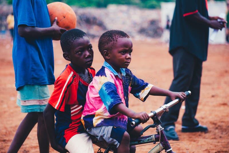 Svarta afrikanska barn som spelar fotboll i en landsbygd arkivbild