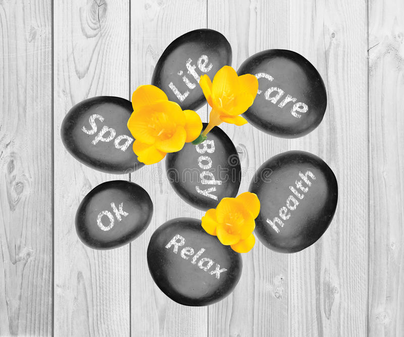 Svarta brunnsortstenar och gula freesiablommor på träbakgrund royaltyfri foto