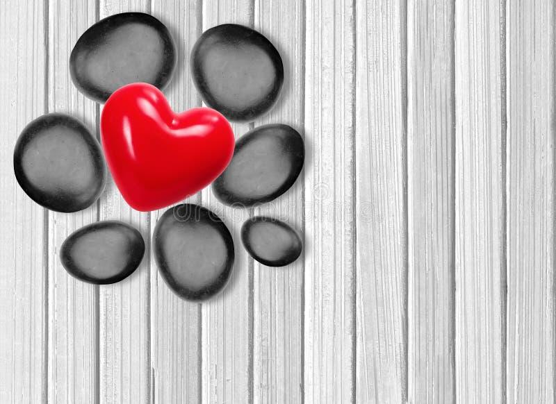 Svarta brunnsortstenar och röd hjärta på vitt trä arkivfoton