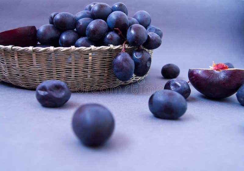 Svarta druvor i en silverkorg p? en gr? bakgrund royaltyfria foton