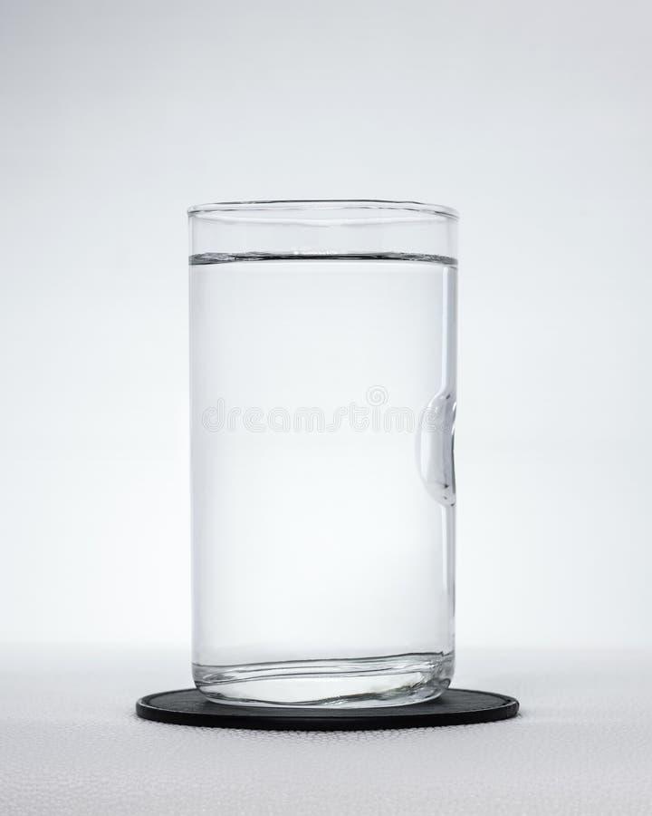Svarta dryckkustfartyg med vattenexponeringsglas på vit bakgrund Rent vatten i genomskinligt exponeringsglas royaltyfri foto