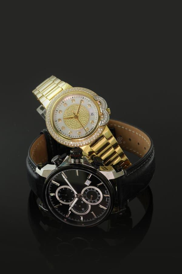 Svarta eleganta två och guld- armbandsur royaltyfria foton