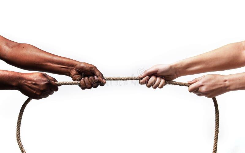Svarta etnicitetarmar med det dragande repet för händer mot den vita Caucasian lopppersonen i stopprasism och xenofobibegrepp arkivbild