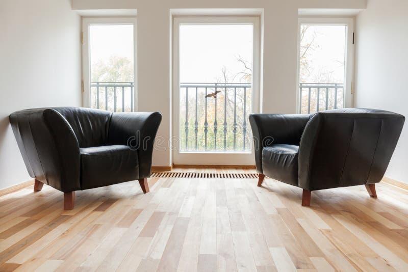 Svarta fåtöljer för läder i ett rum arkivbild