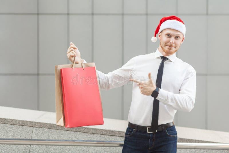 Svarta fredag i vinter Röd head affärsman för lycka i den santa hatten, hållande shoppingpåsar på händer som pekar fingrar och at royaltyfri bild