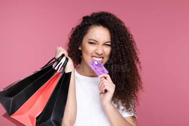 svarta friday Den afro- amerikanska flickan i glasögon rymmer shoppingpåsar och en kreditkort och ler, på en guling arkivbilder