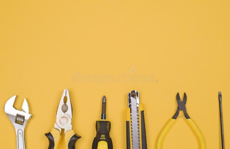 Svarta gula hjälpmedel - kniv, plattång, måttband, skruvmejsel, pojkar på en gul bakgrund placera text Arbetsinventarium arkivbild