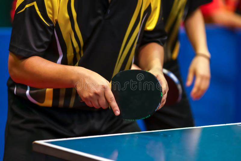 Svarta gula skjortamän som spelar dubbel bordtennis royaltyfri foto