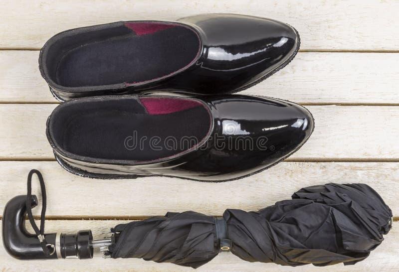 Svarta gummigaloscher med paraplyet på trätabellen royaltyfria foton