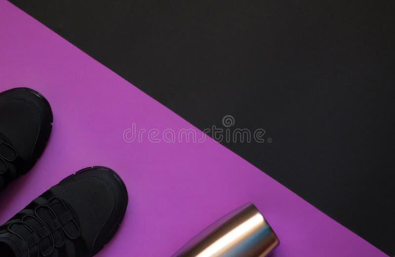 Svarta gymnastikskor och metallflaska på violett och svart geometriskt utrymme för bakgrundswhithkopia royaltyfri bild