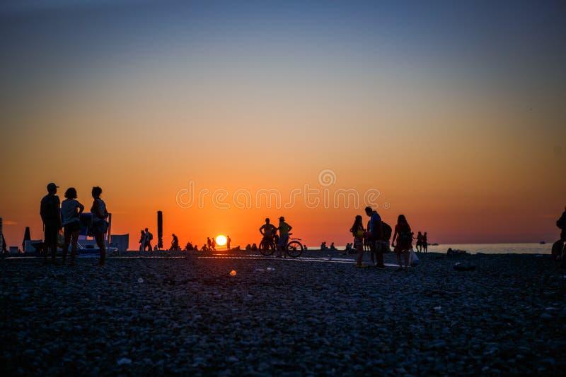 Svarta konturer av folk på stranden i solnedgångljuset av den orange solen arkivbild