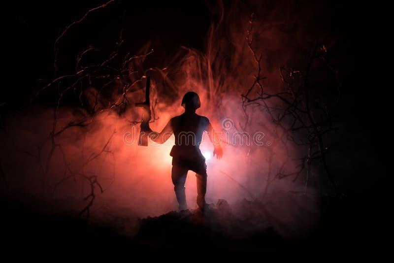 Svarta konturer av soldaten i den brinnande inflyttningen för rökbrand slåss operation tillbaka lampa tonat fotografering för bildbyråer