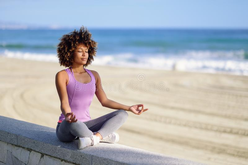 Svarta kvinnan afro frisyr, i lotusblomma poserar med ögon som stängs i stranden fotografering för bildbyråer