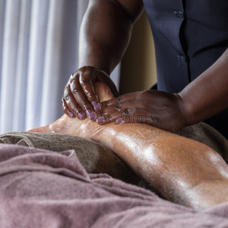 Svarta kvinnan ger en fotmassage till en äldre Caucasian man royaltyfria foton