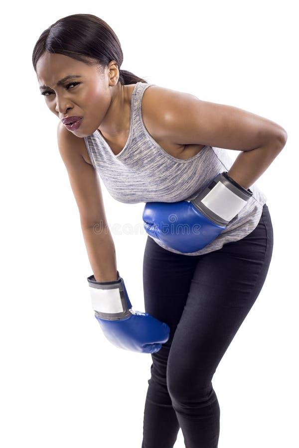 Svarta kvinnliga bärande boxninghandskar som ser gjorde ont arkivbilder