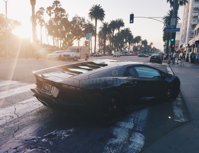 Svarta Lamborghini på solnedgången i Santa Monica California royaltyfri bild
