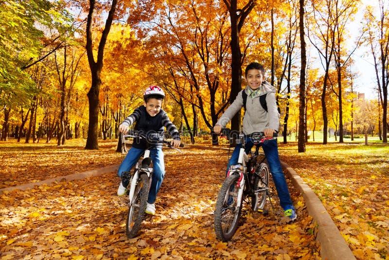 Svarta lyckliga pojkar på cyklar royaltyfria bilder
