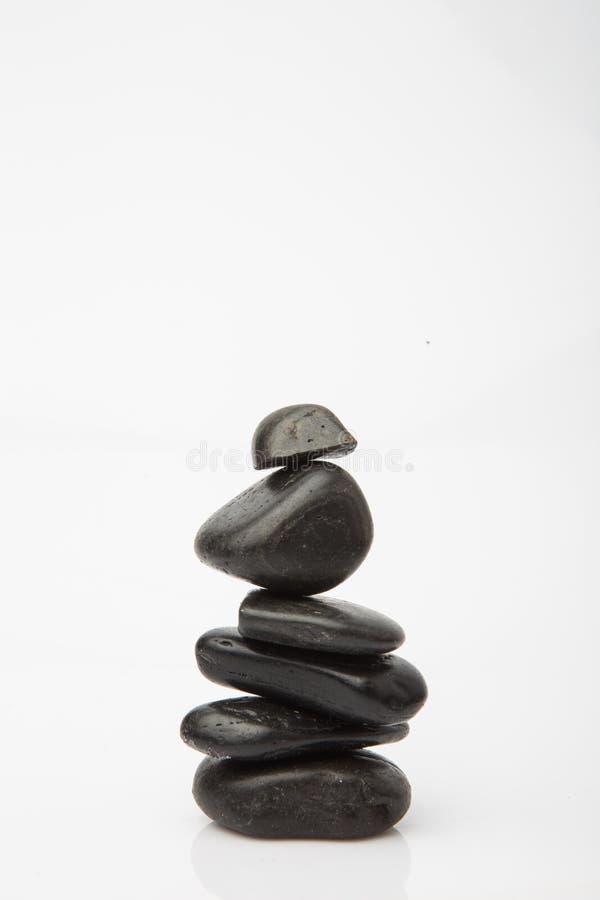 Svarta massagestenar staplade, isolerat på vit Svart sten fotografering för bildbyråer