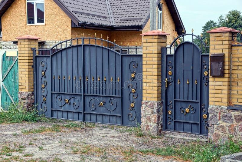 Svarta metallportar och dörrar med en falsk modell och del av en tegelsten fäktar fotografering för bildbyråer