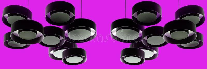 Svarta moderna metalllampor som hänger från ett purpurfärgat tak royaltyfria foton