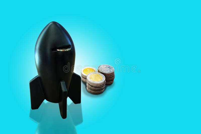 Svarta mynt för ask och för pengar för raketformmynt staplar på pastellfärgad blå bakgrund Spargris i raketform med mynt Snabb ba royaltyfria foton