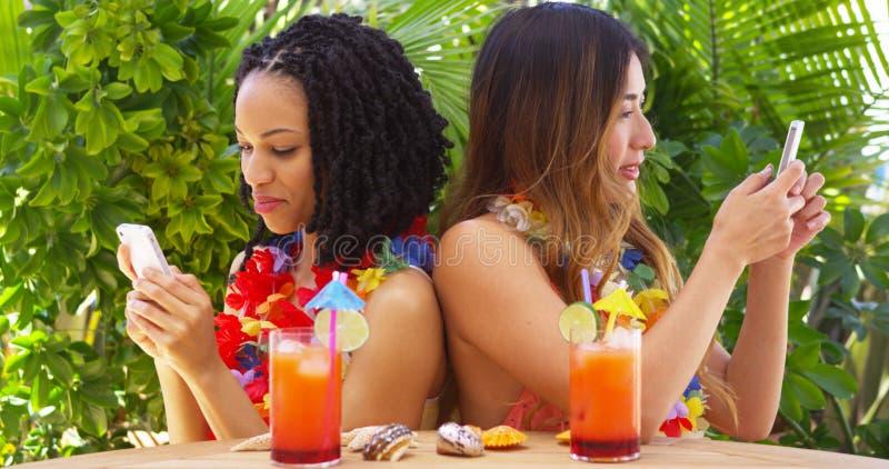 Svarta och asiatiska bästa vän på semester genom att använda mobiltelefoner arkivfoto
