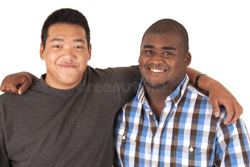 Svarta och asiatiska bröder med armar runt om de som ler royaltyfri foto