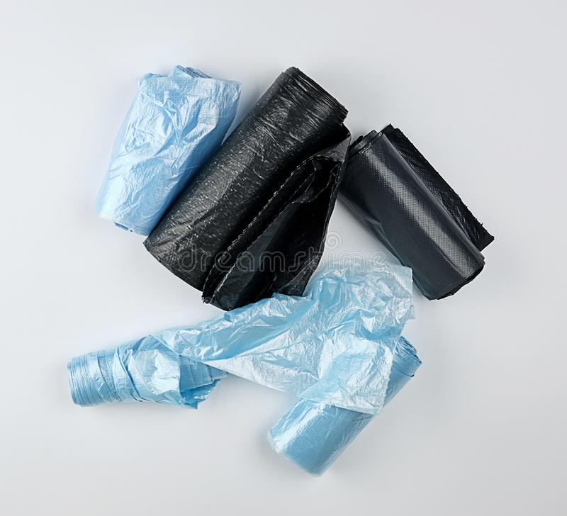 svarta och blåa plastpåsar för soptunna på en vit bakgrund arkivfoto