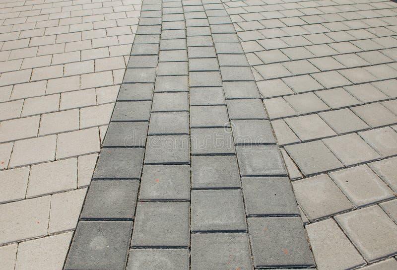Svarta och gråa kullersten av en vandringsled har lagts i en geometrisk modell De är slitna med tid royaltyfria bilder